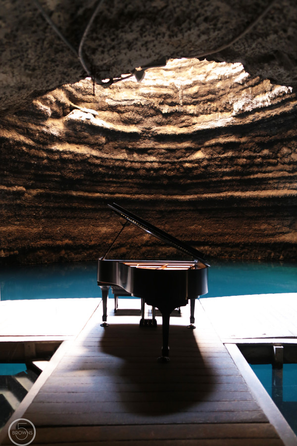 Steinway Piano sitting on dock in geothermal cave.